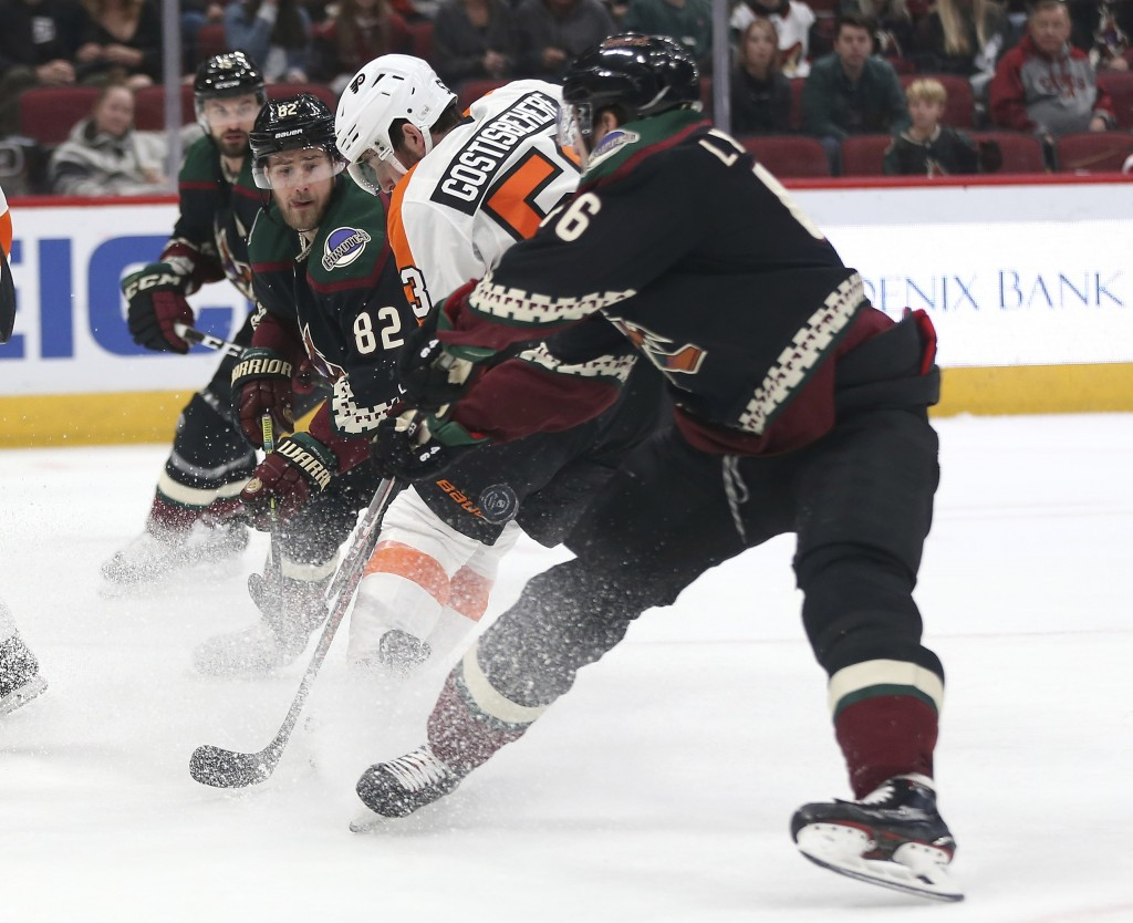Philadelphia Flyers' Shayne Gostisbehere (53) is doubled-teamed by Arizona Coyotes' Jordan Oesterle (82) and Ilya Lybushkin (46) during the first peri...