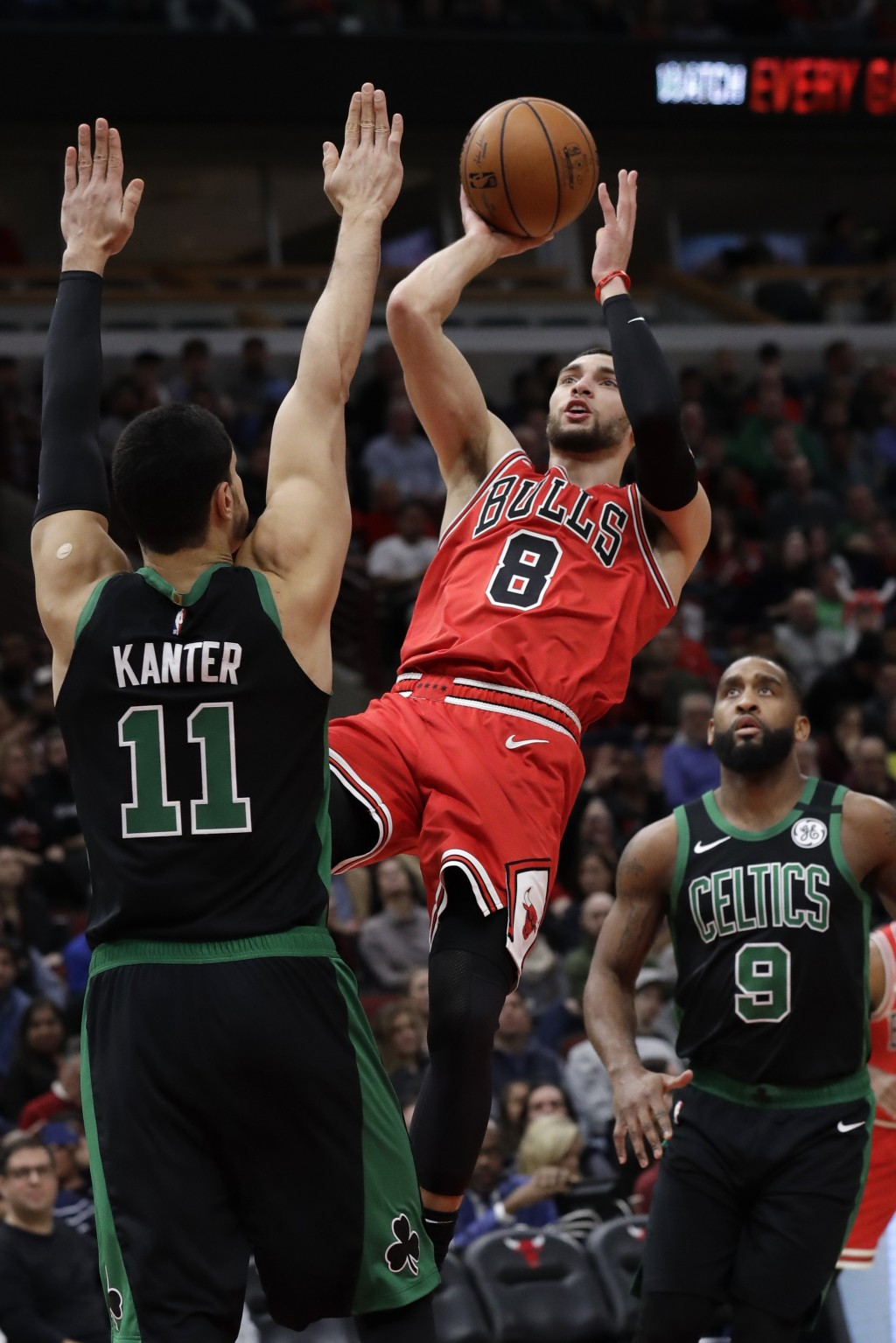 Chicago Bulls guard Zach LaVine (8) shoots over Boston Celtics center Enes Kanter (11) as guard Brad Wanamaker (9) watches during the first half of an...