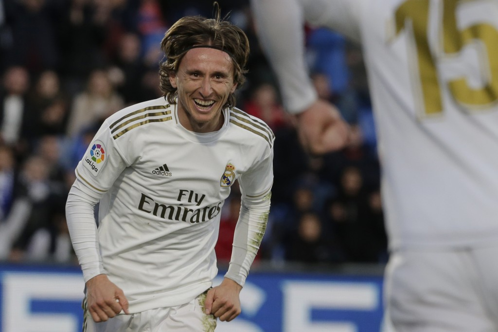 Real Madrid's Luka Modric, left, celebrates with teammate Federico Valverde after scoring his side's third goal during a Spanish La Liga soccer match ...