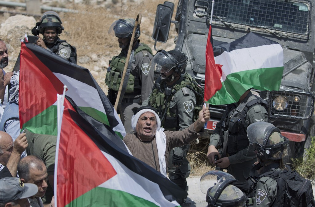 FILE - In this Aug. 16, 2019 file photo, Israeli border police block the road and disperse Palestinian, Israeli and foreign activists during a rally p...