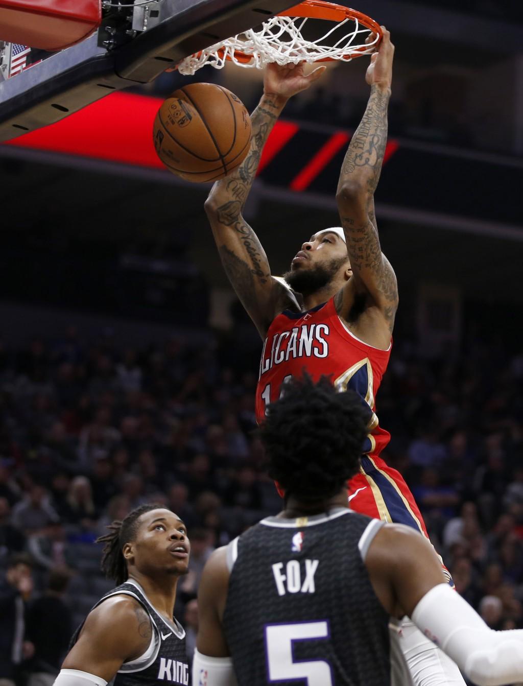 New Orleans Pelicans forward Brandon Ingram, center, dunks between Sacramento Kings' Richaun Holmes, left, and De'Aaron Fox during the first quarter o...