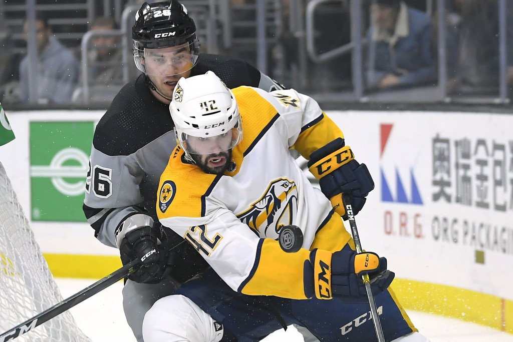 Nashville Predators center Colin Blackwell, right, works for the puck against Los Angeles Kings defenseman Sean Walker during the first period of an N...
