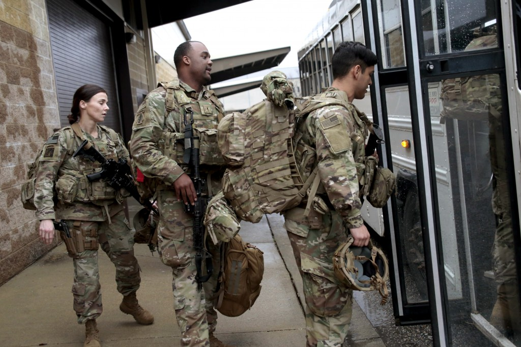 U.S. Army soldiers with their gear board an awaiting bus Saturday, Jan. 4, 2020 at Fort Bragg, N.C., as troops from the 82nd Airborne are deployed to ...