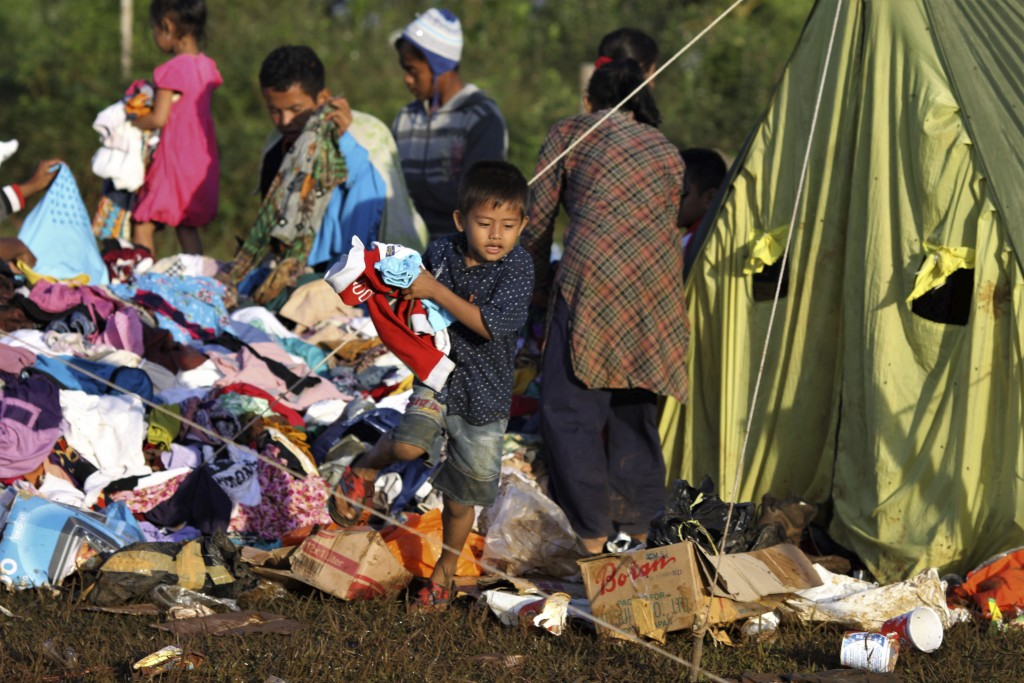 A young boy holds clothings he picked from a pile of relief goods at a temporary shelter for people who are affected by landslide, in Bogor, West Java...