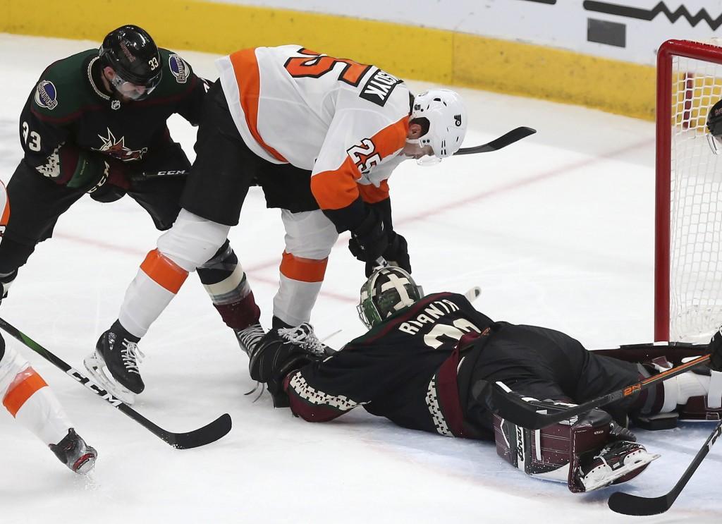 Arizona Coyotes goalie Antti Raanta (32) falls on the puck as Philadelphia Flyers' James van Riemsdyk (25) fights for it while Coyotes' Alex Goligoski...