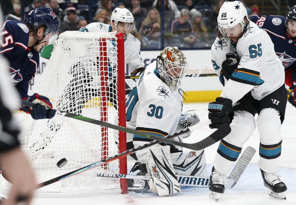 San Jose Sharks' Aaron Dell, center, makes a save between Erik Karlsson, right, of Sweden, and Columbus Blue Jackets' Jakob Lilja, of Sweden, during t...
