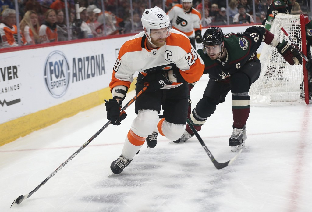 Philadelphia Flyers' Claude Giroux (28) loses control of the puck as Arizona Coyotes' Oliver Ekman-Larsson (23) closes in on him during the first peri...