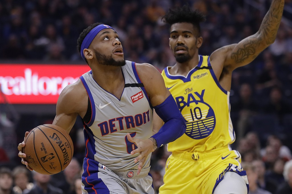 Detroit Pistons' Bruce Brown, left, looks to shoot against Golden State Warriors' Jacob Evans (10) during the first half of an NBA basketball game Sat...