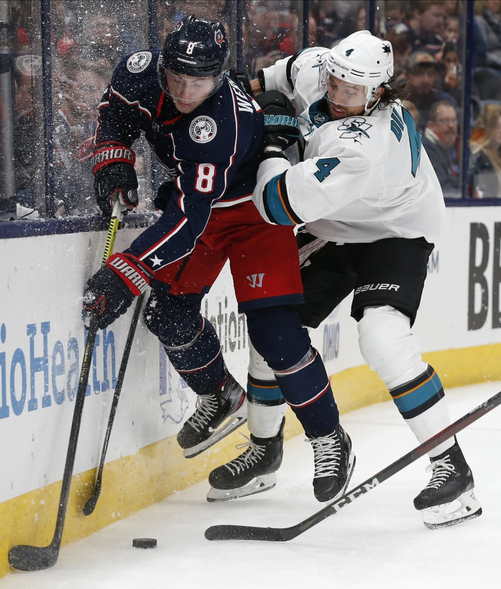 San Jose Sharks' Brenden Dillon, right, checks Columbus Blue Jackets' Zach Werenski during the second period of an NHL hockey game Saturday, Jan. 4, 2...