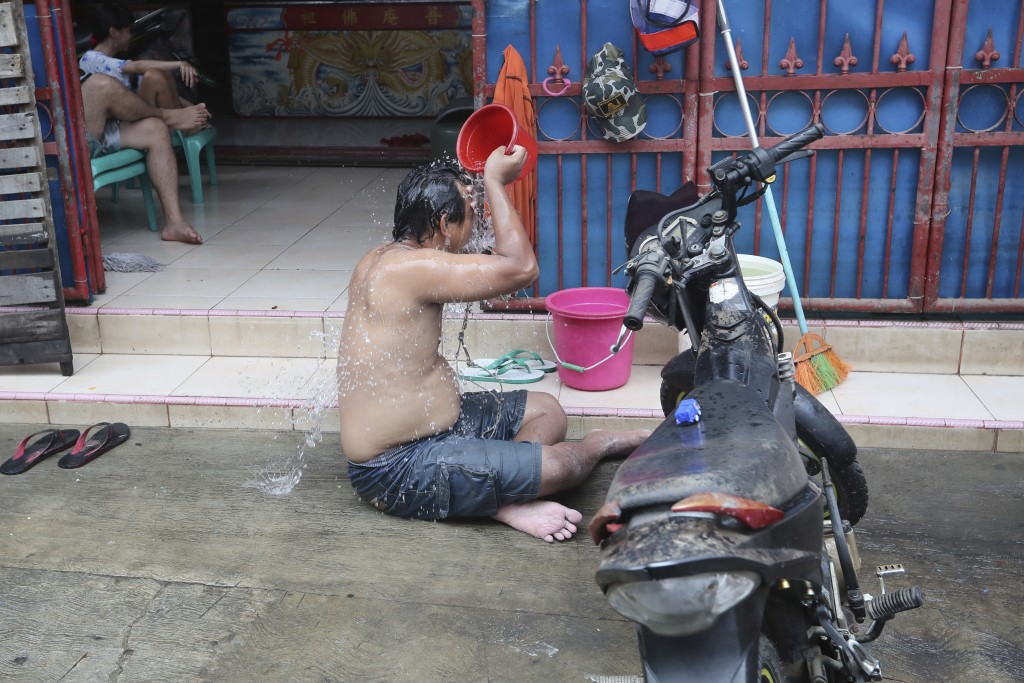 A man takes a shower in front of his flood-damaged house in Jakarta, Indonesia, Sunday, Jan. 5, 2020. Landslides and floods triggered by torrential do...