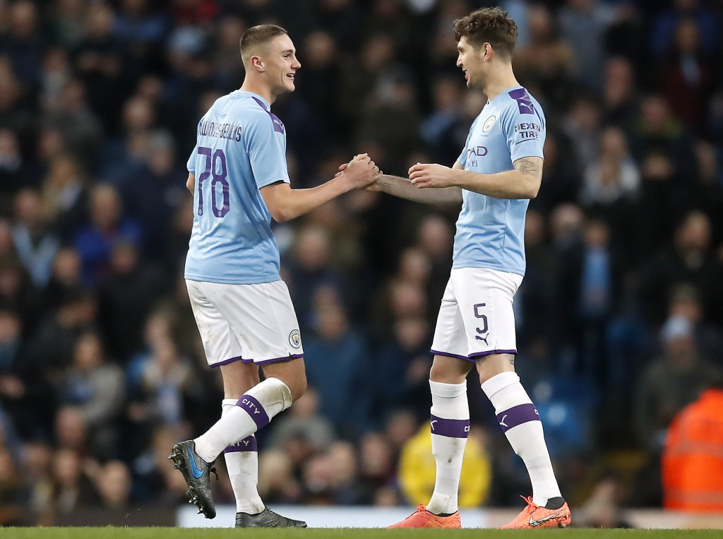 Manchester City's Taylor Harwood-Bellis, right, celebrates scoring his side's third goal of the game with teammate John Stones during the English FA C...