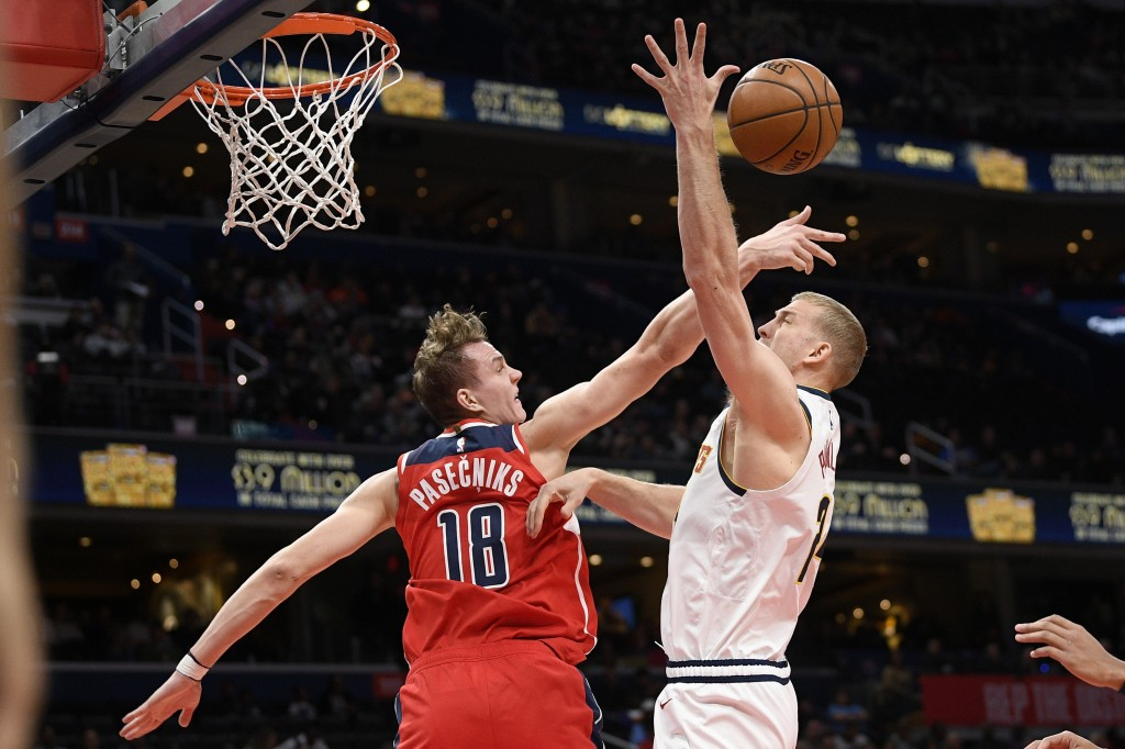 Washington Wizards center Anzejs Pasecniks (18) and Denver Nuggets forward Mason Plumlee, right, battle for the ball during the first half of an NBA b...