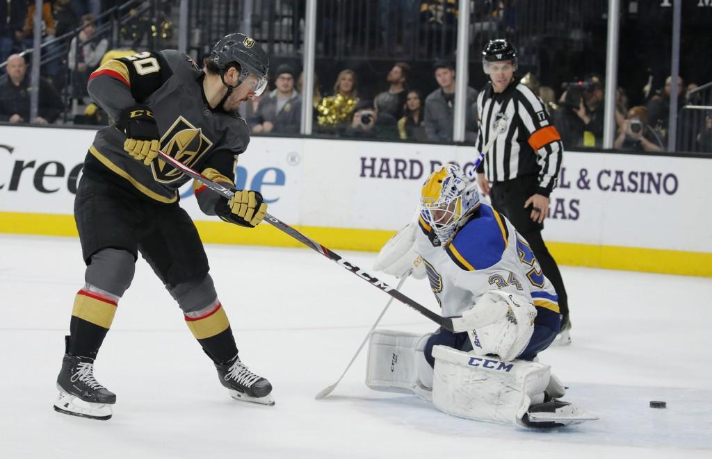 Vegas Golden Knights center Chandler Stephenson (20) scores on St. Louis Blues goaltender Jake Allen (34) to win an NHL hockey game during overtime Sa...