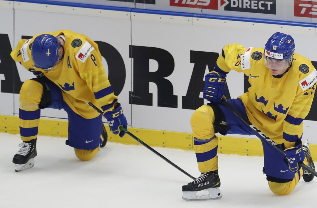 Sweden's Rasmus Sandin, left, and Sweden's Oskar Back, right, kneel on ice after loosing the U20 Ice Hockey Worlds semifinal match between Sweden and ...