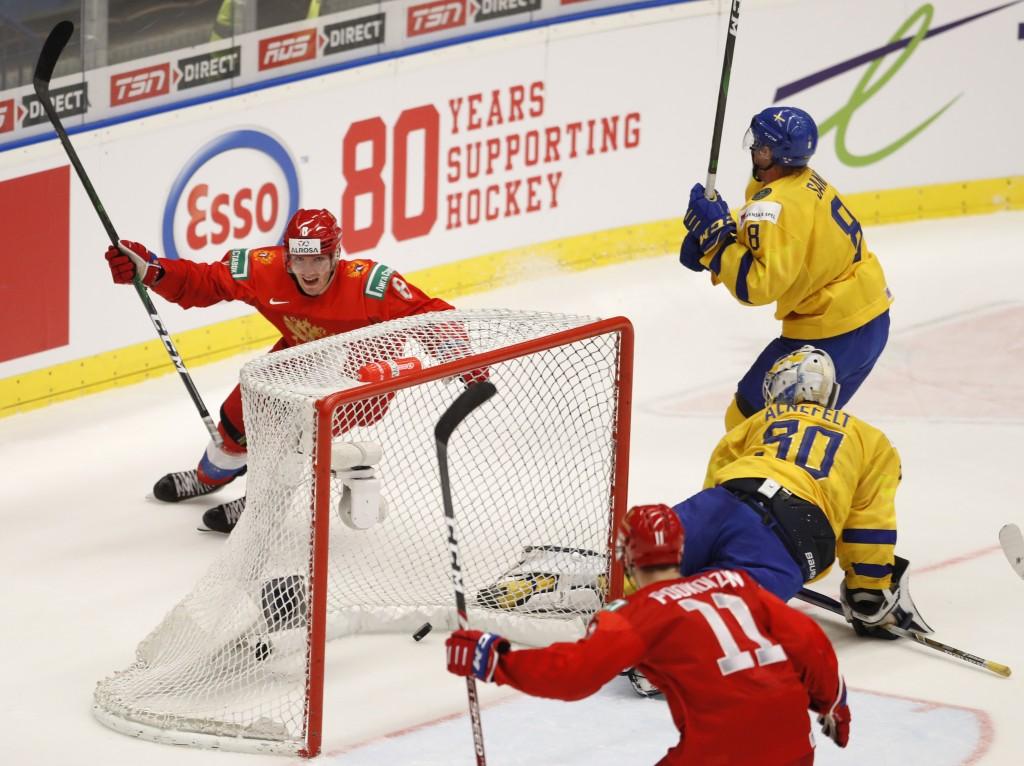 Russia's Ivan Morozov, left, celebrates after scoring his sides winning goal past Sweden's goaltender Hugo Alnefelt, center right, during the U20 Ice ...