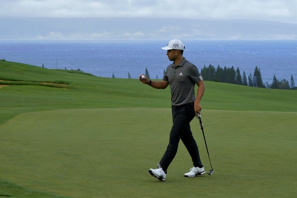 Xander Schauffele acknowledges the gallery after putting on the fourth green during third round of the Tournament of Champions golf event, Saturday, J...