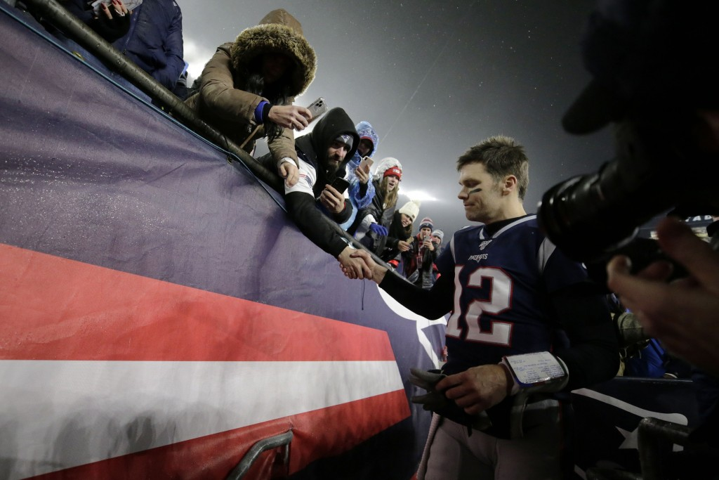 New England Patriots quarterback Tom Brady shakes hands with a fan as he leaves the field after losing an NFL wild-card playoff football game to the T...
