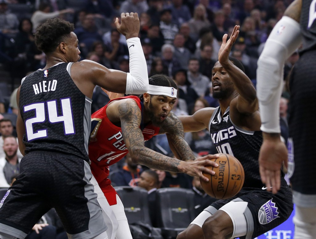 New Orleans Pelicans forward Brandon Ingram, center, tries to squeeze through double-team pressure by Sacramento Kings' Buddy Hield, left and Harrison...