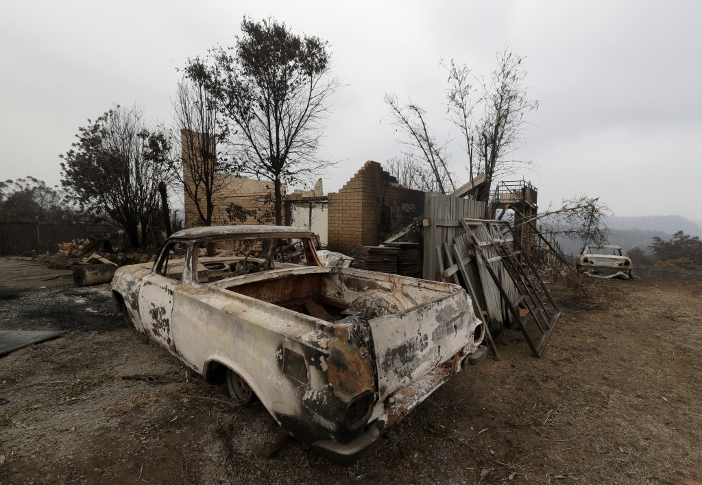 A truck is burnt out and a house destroyed at Conjola Park, Australia, Sunday, Jan. 5, 2020, after recent wildfires ripped through the community. The ...