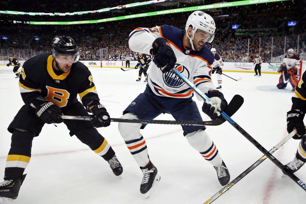 Edmonton Oilers' Riley Sheahan (23) defends against Boston Bruins' Brad Marchand (63) during the first period on an NHL hockey game in Boston, Saturda...