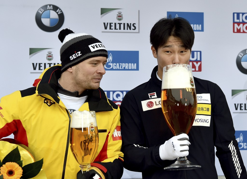 Yun Sung Bin from South Korea zips from a giant glass of beer after winning the men's Skeleton world cup in Winterberg, Germany, Sunday, Jan.5, 2019. ...
