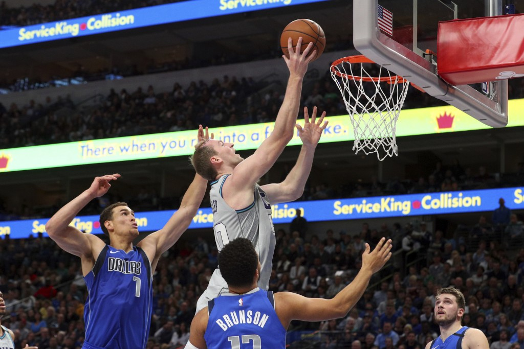 Dallas Mavericks forward Dwight Powell (7) and guard Jalen Brunson (13) try to defend against a shot by Charlotte Hornets forward Cody Zeller (40) in ...