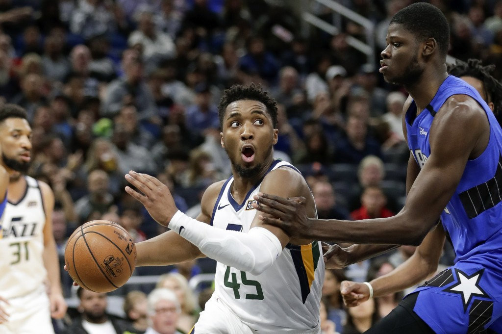 Utah Jazz guard Donovan Mitchell (45) drives around Orlando Magic center Mo Bamba during the second half of an NBA basketball game, Saturday, Jan. 4, ...