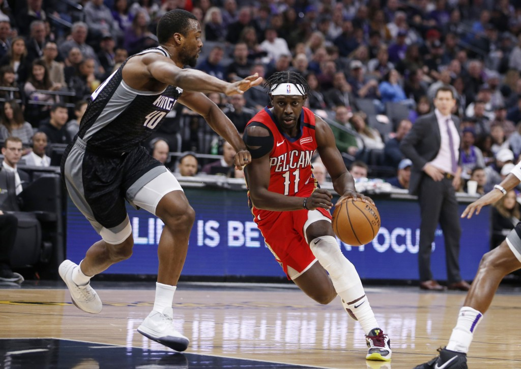 New Orleans Pelicans guard Jrue Holiday, right, drives against Sacramento Kings forward Harrison Barnes during the first quarter of an NBA basketball ...