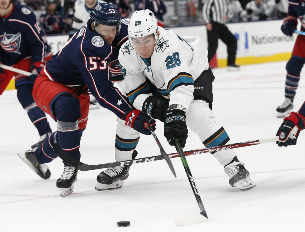 Columbus Blue Jackets' Gabriel Carlsson, left, of Sweden, and San Jose Sharks' Timo Meier, of Switzerland, battle for the puck during the first period...