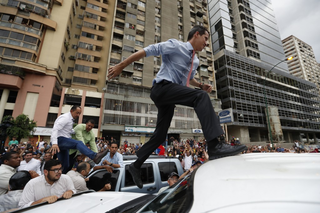 FILE - In this March 12, 2019 file photo, National Assembly President Juan Guaido, who declared himself interim president of Venezuela, leaps on to a ...