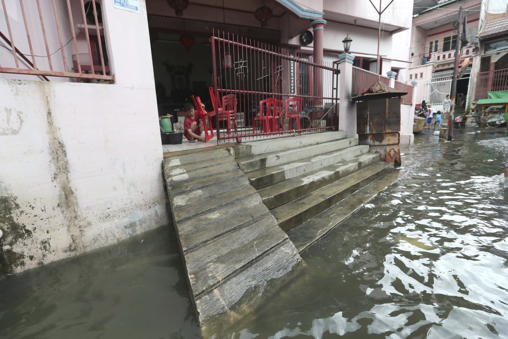 A woman cleans her flood-damaged house in Jakarta, Indonesia, Sunday, Jan. 5, 2020. Landslides and floods triggered by torrential downpours have left ...