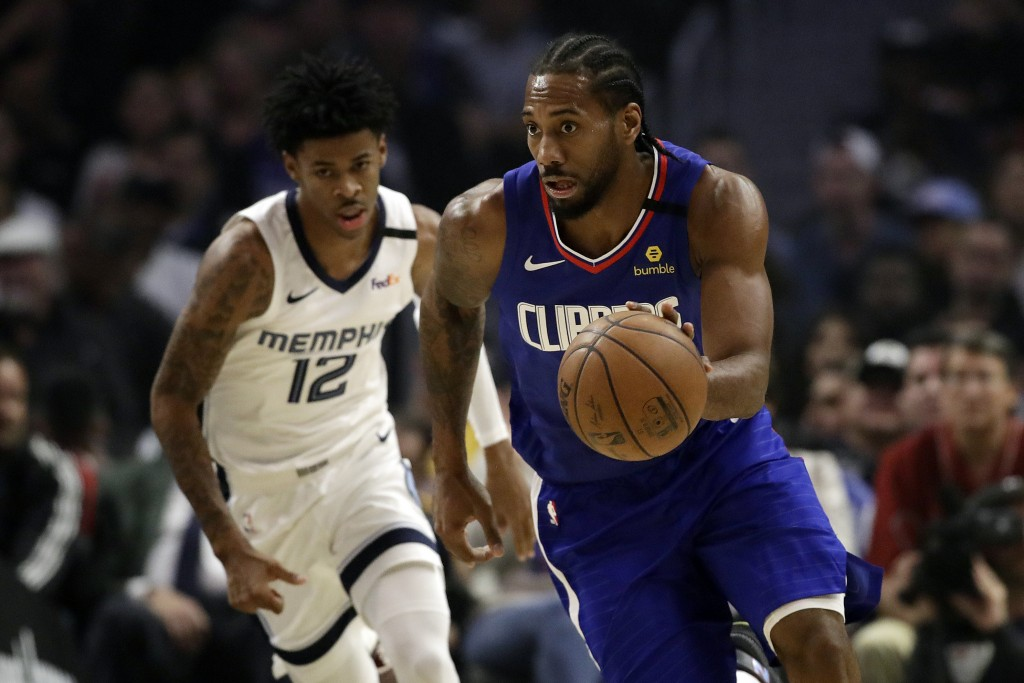 Los Angeles Clippers' Kawhi Leonard, right, dribbles past Memphis Grizzlies' Ja Morant (12) during the first half of an NBA basketball game Saturday, ...