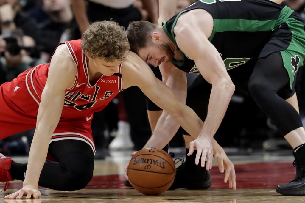 Chicago Bulls forward Lauri Markkanen, left, and Boston Celtics forward Gordon Hayward compete for the ball during the first half of an NBA basketball...