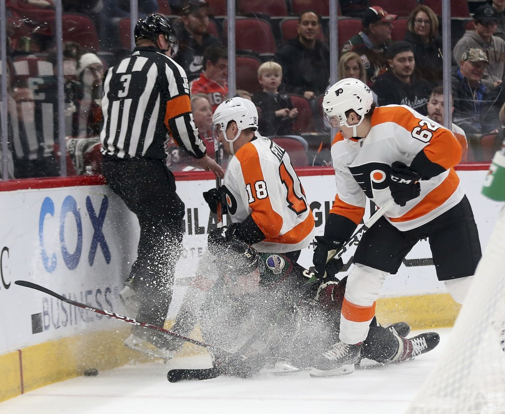 Arizona Coyotes' Jakob Chychrun (6) goes down as he gets sandwiched between Philadelphia Flyers' Tyler Pitlick (18) and Nicolas Aube-Kubel (62) during...