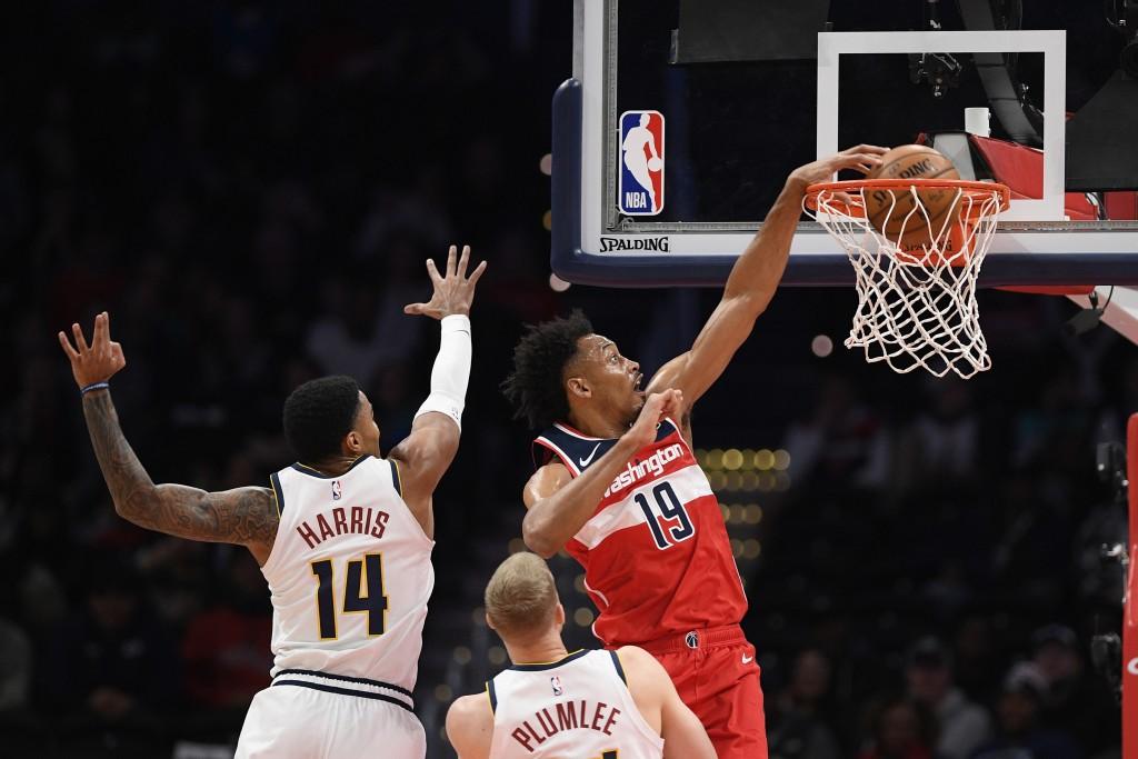 Washington Wizards forward Johnathan Williams (19) dunks past Denver Nuggets guard Gary Harris (14) and forward Mason Plumlee (24) during the first ha...