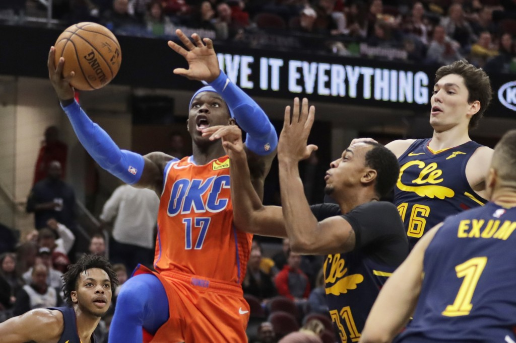 Oklahoma City Thunder's Dennis Schroder (17) drives against Cleveland Cavaliers' John Henson (31) in the second half of an NBA basketball game, Saturd...