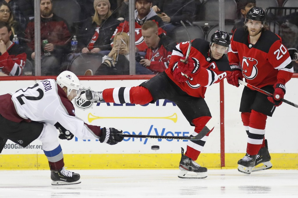New Jersey Devils defenseman Andy Greene (6) tries to pass past Colorado Avalanche right wing Joonas Donskoi (72), of Finland, during the second perio...