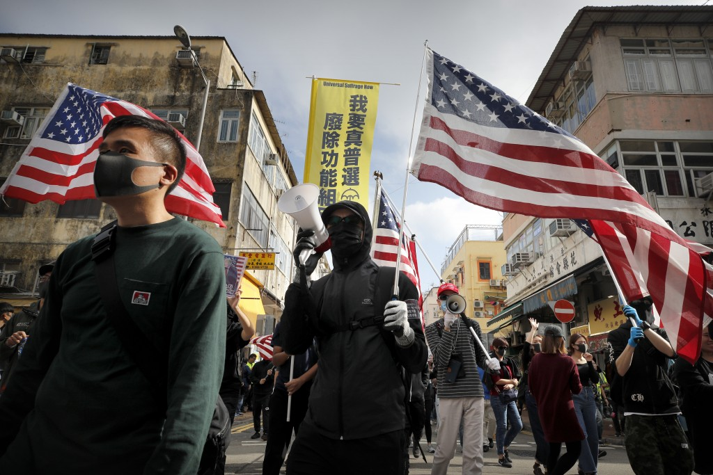 "Protesters carry U.S. flags as they march during a demonstration against ""parallel traders"" who buy goods in Hong Kong to resell in mainland China in ..."