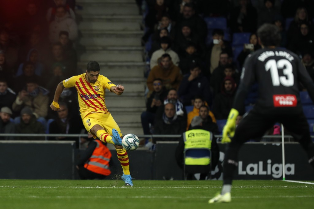 Barcelona's Luis Suarez, left, passes the ball during the Spanish La Liga soccer match between Espanyol and Barcelona at the RCDE Stadium in Barcelona...