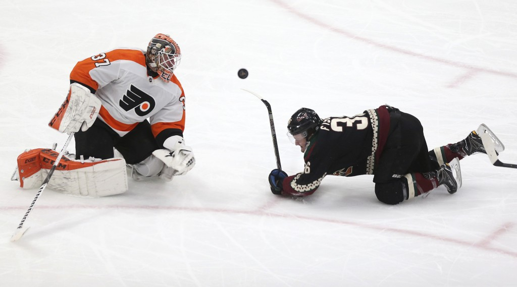 Philadelphia Flyers goalie Brian Elliott (37) watches the puck as it comes off Arizona Coyotes' Christian Fischer's (36) stick during the second perio...