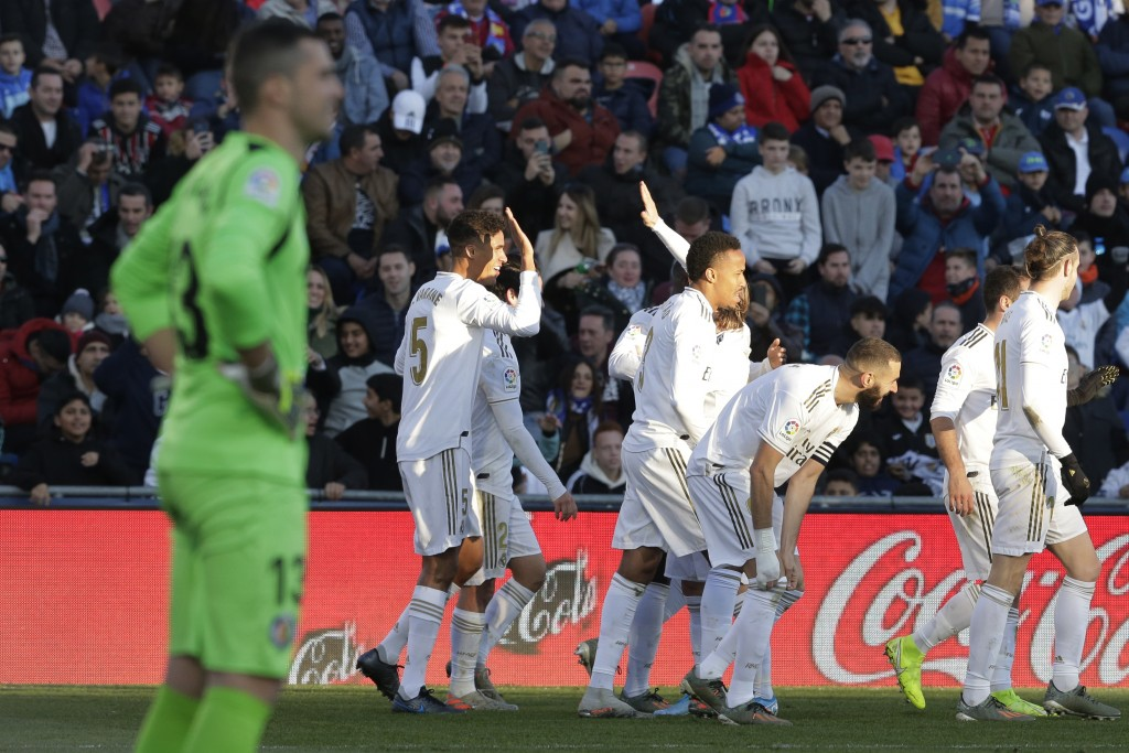 Real Madrid's Raphael Varane, rear left, celebrates after scoring his side's second goal during a Spanish La Liga soccer match between Getafe and Real...