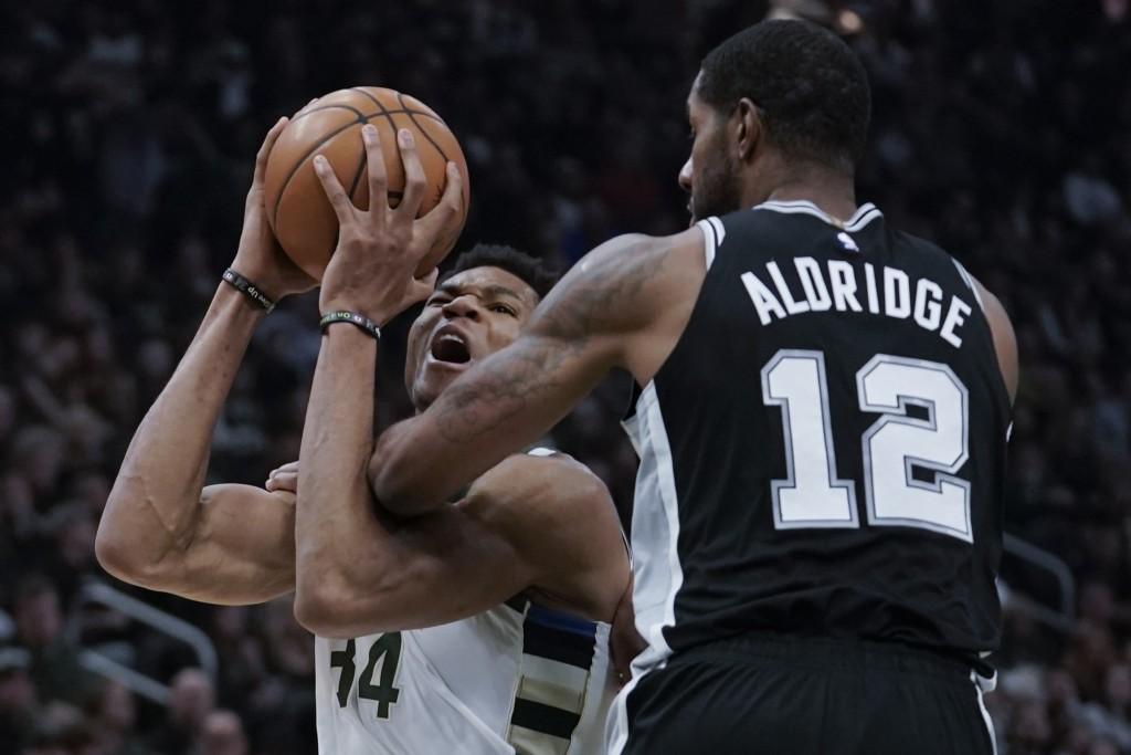 Milwaukee Bucks' Giannis Antetokounmpo is fouled by San Antonio Spurs' LaMarcus Aldridge during the first half of an NBA basketball game Saturday, Jan...