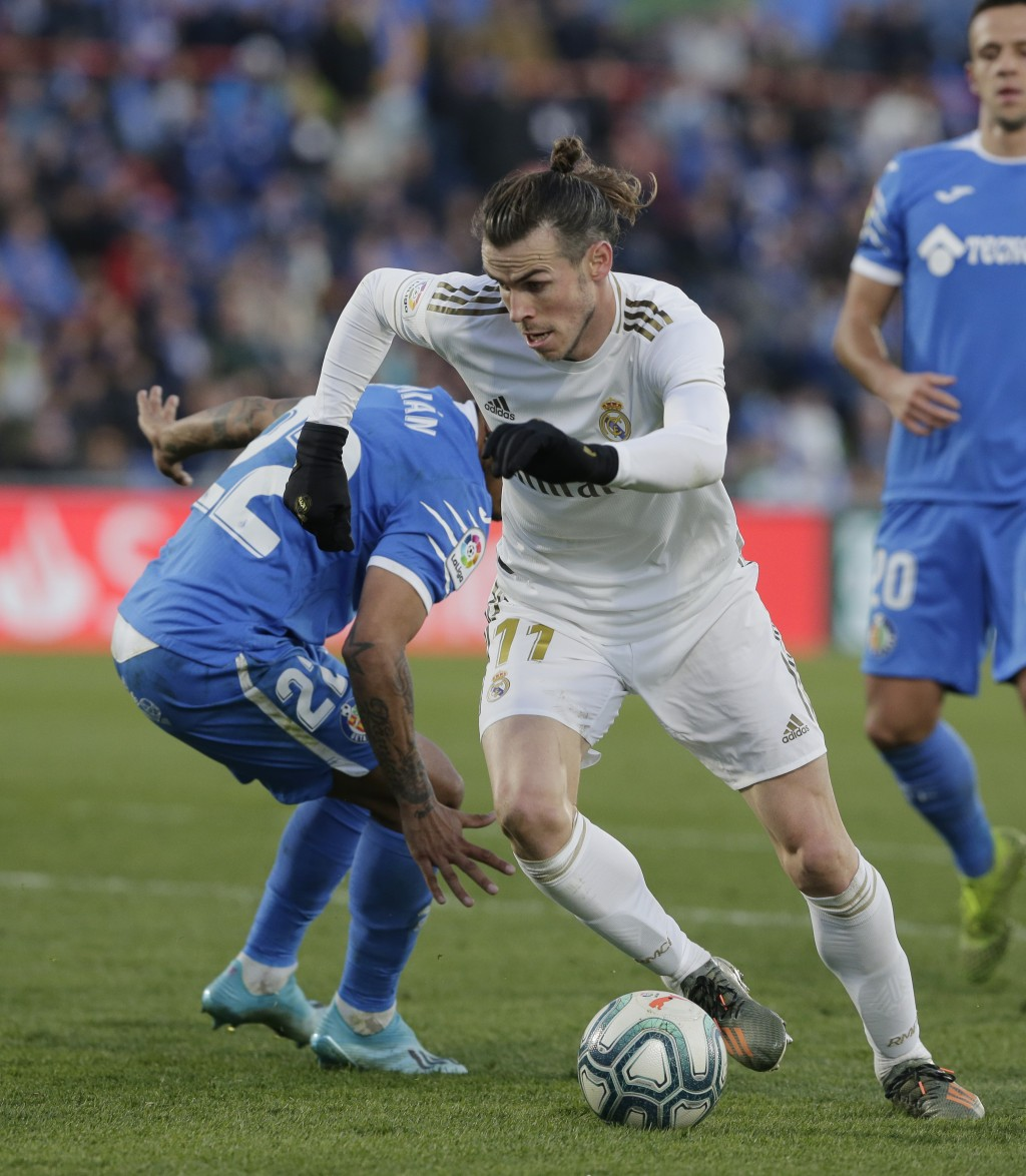 Real Madrid's Gareth Bale, right, dribbles through the defence during a Spanish La Liga soccer match between Getafe and Real Madrid at the Coliseum Al...
