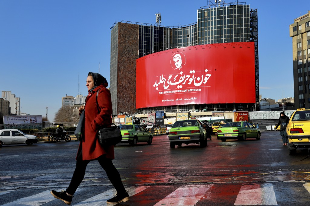A woman crosses a street in front of a billboard showing a portrait of Iranian Revolutionary Guard Gen. Qassem Soleimani, who was killed in a U.S. air...