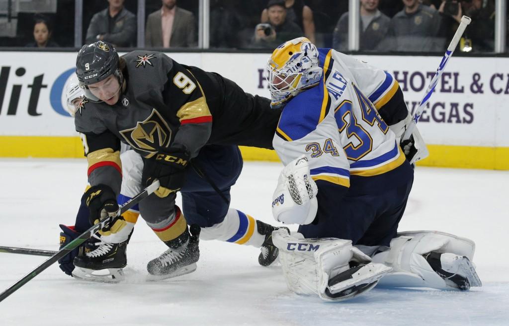 St. Louis Blues goaltender Jake Allen (34) blocks a shot beside Vegas Golden Knights center Cody Glass (9) during the second period of an NHL hockey g...