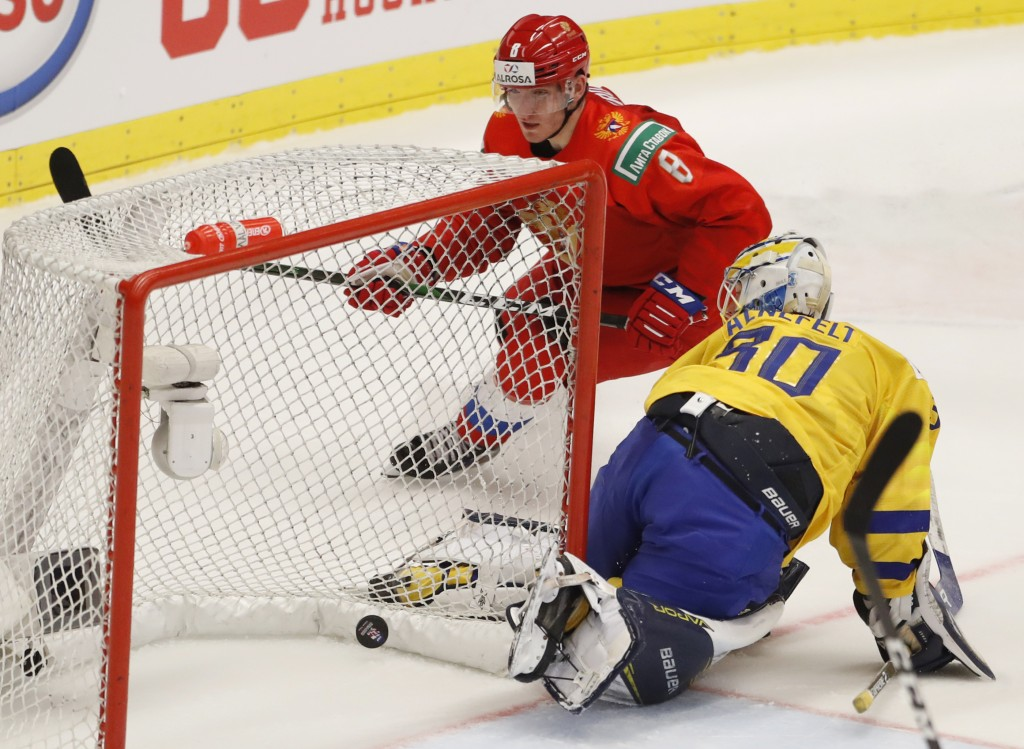 Russia's Ivan Morozov, left, scores his sides winning goal past Sweden's goaltender Hugo Alnefelt, right, during the U20 Ice Hockey Worlds semifinal m...