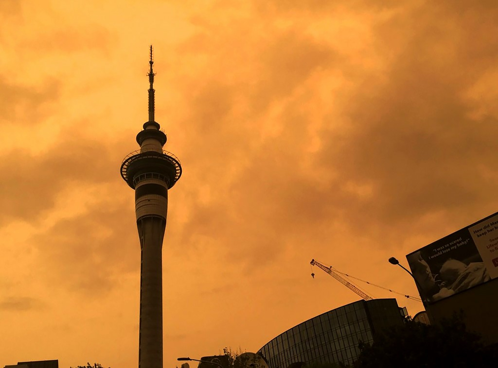 The sky above Auckland's Sky Tower turns orange as smoke from the Australia wildfires arrives in New Zealand, Sunday, Jan. 5, 2020. Australian Prime M...