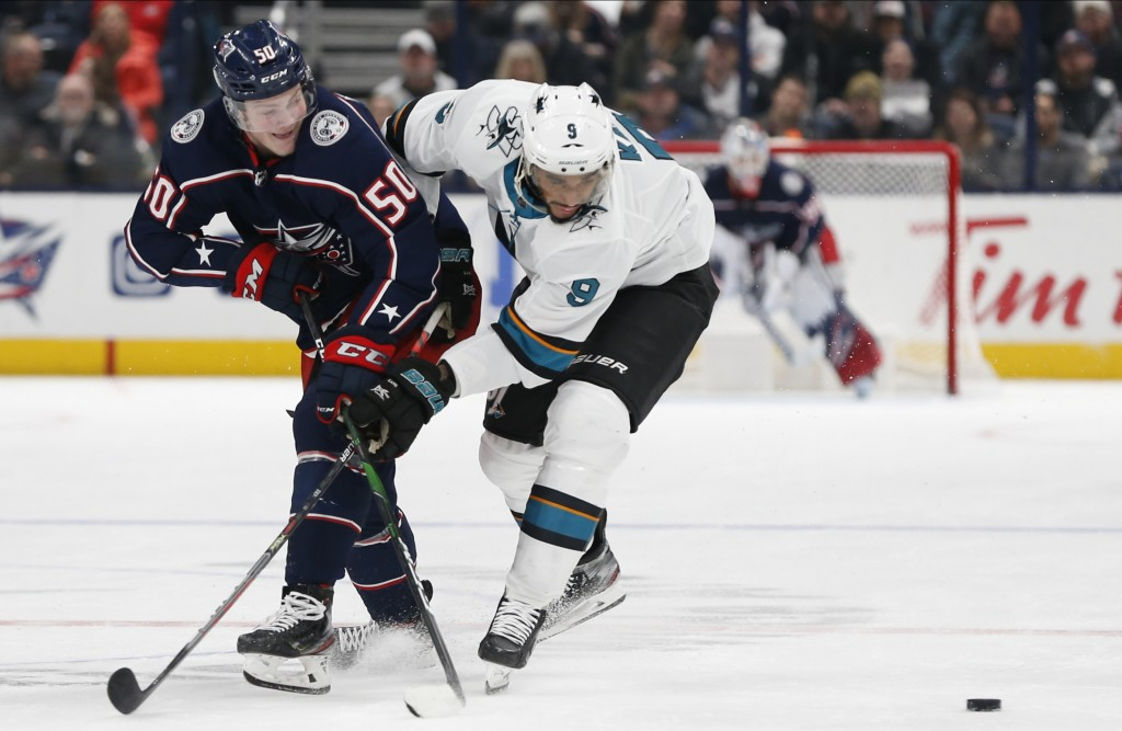 Columbus Blue Jackets' Eric Robinson, left, passes the puck in front of San Jose Sharks' Evander Kane during the second period of an NHL hockey game S...