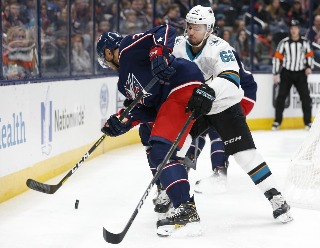 Columbus Blue Jackets' Seth Jones, left, tries to clear the puck as San Jose Sharks' Kevin Labanc defends during the first period of an NHL hockey gam...