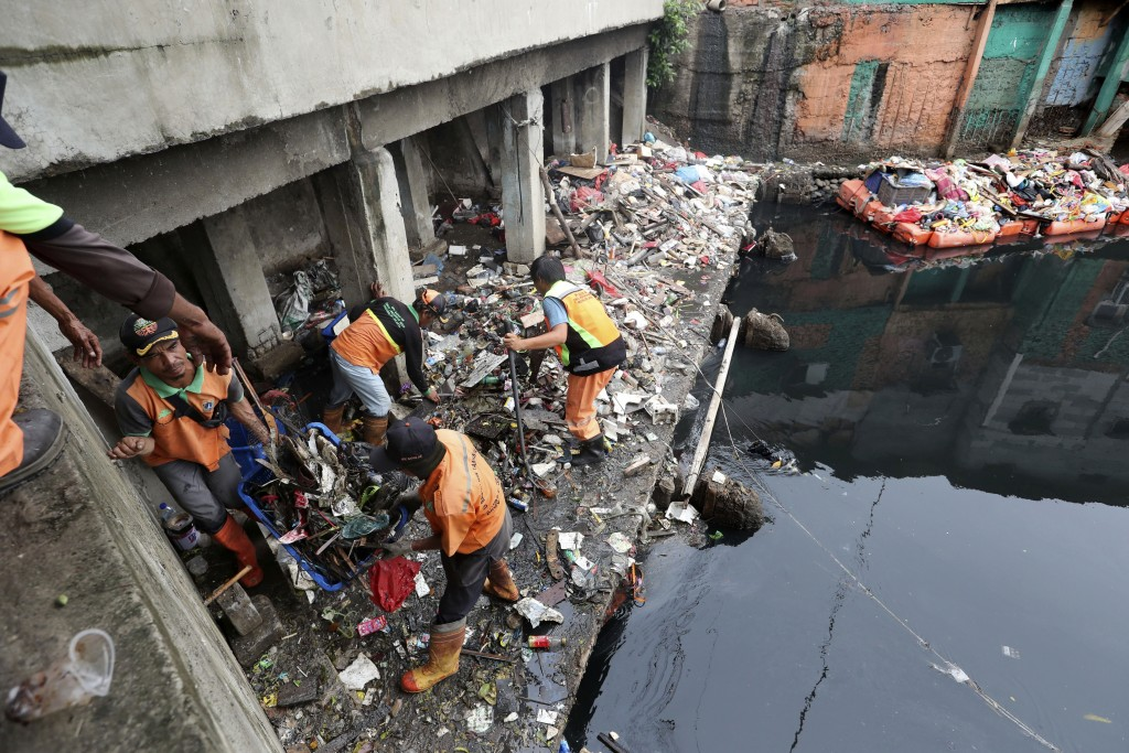 Workers collect trash during a clean-up after flood in Jakarta, Indonesia, Sunday, Jan. 5, 2020. Landslides and floods triggered by torrential downpou...
